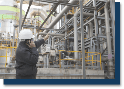 construction worker observing pipes in a plant