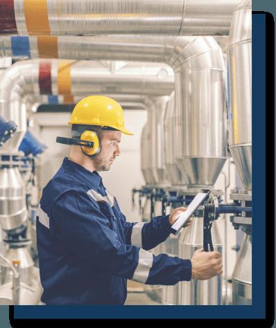 worker inspecting pressure valves on an indoor pipeline