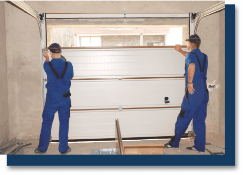 two workers installing a garage door
