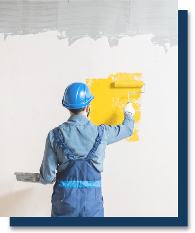 worker painting a wall yellow
